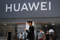 People walk past a Huawei retail store in Beijing, on June 30, 2019. (AP Photo/Andy Wong)