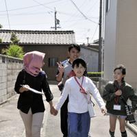 バディーの子どもたちと手をつなぎ、スタンプラリーをする技能実習生たち=愛知県高浜市で、太田敦子撮影