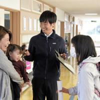 保護者引き渡し訓練で待ちわびる佐藤双波さん(右)を母恵美さんが迎えに来た。阿部航大教諭(中央)も安心し、みな笑みがこぼれた=宮城県石巻市の東浜小で