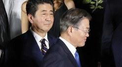 集合写真の撮影を前に、安倍晋三首相(中央)の前を歩く韓国の文在寅大統領(右)=大阪市中央区で2019年6月28日、代表撮影