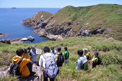 植生の回復具合などについて説明を聞く参加者ら=石川県輪島市沖で、阿部弘賢撮影