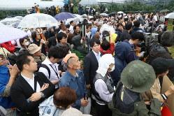 参院選が公示され、雨の中で候補者の演説を聞く人たち=福島市で2019年7月4日午前10時21分、小川昌宏撮影