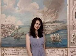 任正非氏の次女、姚安娜氏。米独立戦争の「ボストン包囲戦」の絵画を背にした微笑が意味深だ。(姚安娜氏のインスタグラムから)