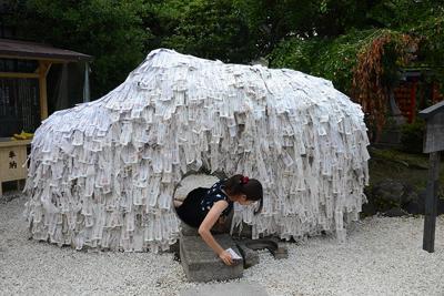 縁切り縁結び碑をくぐる女性=京都市東山区の安井金比羅宮で、道岡美波撮影