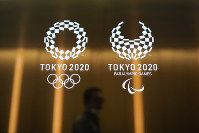 In this June 11, 2019 file photo, a man walks past the Tokyo 2020 Olympic and Paralympic logos, in Tokyo. (AP Photo/Jae C. Hong)