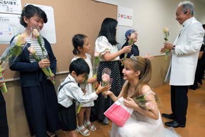 楽屋を訪問した子供たちから花を受け取るサラ・オレインさん(手前右)と、谷村新司さん(右端)=東京都渋谷区のBunkamuraオーチャードホールで5日、手塚耕一郎撮影