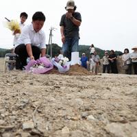 土石流が押し寄せた川沿いで行われた犠牲者の追悼行事で花を手向ける地元住民たち=広島県呉市安浦地区で2019年7月5日午後1時19分、小出洋平撮影