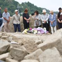 土石流が押し寄せた川沿いで花束を供え、犠牲者を追悼する地元住民ら=広島県呉市で2019年7月5日午後1時34分、小出洋平撮影