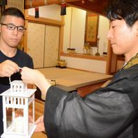 神戸市から運んだ「1.17希望の灯り」を手渡す上垣内知洋さん(左)=広島県坂町小屋浦で、池田一生撮影