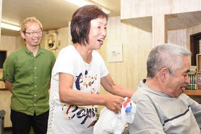 長男宙さん(左)の理髪店で働く兵頭千恵さん(中央)。なじみの客の散髪を終え、「また来てね」と笑顔を見せた=愛媛県西予市野村町地区で2019年6月14日、中川祐一撮影