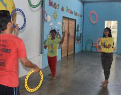 輪投げの練習をするカスマさん(右)とダビド・ヤシンさん(中央)=ジャカルタ北部チリンチンで2019年7月3日、武内彩撮影