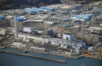 Decommissioning works are seen continuing at the Fukushima Daiichi Nuclear Power Station, in Okuma, Fukushima Prefecture, in this image taken from a Mainichi Shimbun helicopter on Feb. 14, 2019. A multitude of treated water storage tanks can be seen behind the reactor buildings. (Mainichi/ Koichiro Tezuka)