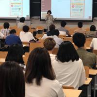 大学生ら参加者に、夫婦別姓をめぐる体験談を語る小国綾子記者=梶山玉香さん撮影