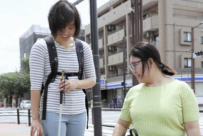 点字ブロックのそばに車止めのポールがあり、「歩行の際に危険ではないか」と指摘する大日方さん(右)と高田さん=東京都調布市で
