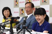 Sumire Nakamura, right, smiles at a press conference after clinching her first official match victory, in Osaka's Kita Ward on July 8, 2019. At left is her opponent, fourth-dan ranked player Chieko Tanaka, and in the center is ninth-dan ranked Kunio Ishii, who acted as an observer of the game. (Mainichi/Rei Kubo)