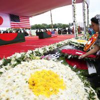 事件で亡くなった犠牲者の追悼式で花を手向ける参列者=ダッカで16年7月4日