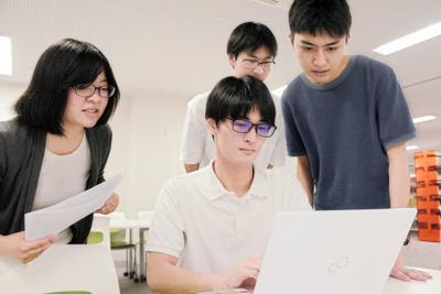 回答を分析する鴫原宏一朗さん(中央)ら東北大の学生たち=仙台市青葉区で8日