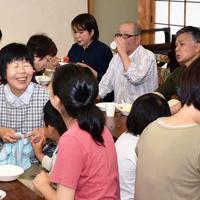 鳥取県内の里親と里子の交流会で、食卓を囲み談笑する参加者=鳥取県北栄町で2019年6月、園部仁史撮影