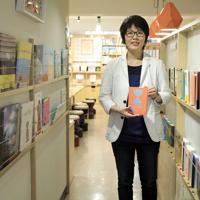 「クオン」の社長、金承福さん。本のトンネルを抜けるとブックカフェになっている=東京都千代田区で、梅村直承撮影