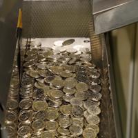 圧印機から次々と出てくる天皇陛下即位記念の500円硬貨=大阪市北区の造幣局で2019年7月11日午後2時48分、大西達也撮影