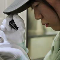 圧印機から次々と出てくる令和元年の500円硬貨をルーペで調べる職員=大阪市北区の造幣局で2019年7月11日午後2時58分、大西達也撮影