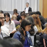 さまざまな言語の通訳を介し、高校入試についての説明を聞く親子ら=文京区の東洋大で
