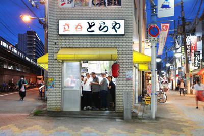 大阪市福島区福島7。たそがれ時、常連客で混み合う「とらや」。商店街入口に、にぎやかな会話が響く=2019年7月9日、小出洋平撮影