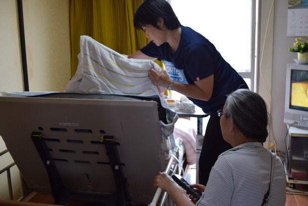 寝たきりの高齢女性の世話をするヘルパーと田中良枝さん(右手前)=連載「介護崩壊」より