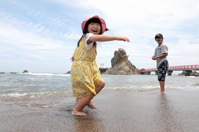 9年ぶりの海開きの日を迎えた久之浜・波立海水浴場の波打ち際で遊ぶ子どもたち=福島県いわき市で2019年7月13日午前11時12分、和田大典撮影