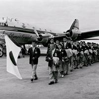 五輪旗や「Olympic Special」の文字が描かれた日本航空の特別機「蔵王号」でメルボルンのエッセンドン空港に到着したメルボルン五輪日本選手団の第1陣。手前左から2人目は田畑政治選手団長=オーストラリア・メルボルンのエッセンドン空港で1956年(昭和31年)11月6日、石井清特派員撮影