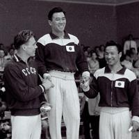 メルボルン五輪男子体操個人種目別鉄棒の表彰台に立ち、健闘を称え合う左から銀メダルを獲得したソ連のチトフ選手、金メダルの小野喬選手、銅メダルの竹本正男選手=オーストラリア・メルボルンの西メルボルンスタジアムで1956年(昭和31年)12月7日、石井清特派員撮影