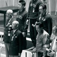 競泳男子200㍍平泳ぎで優勝、表彰式で国旗掲揚を見る金メダルを手にした古川勝選手(表彰台中央)と銀メダルの吉村昌弘選手(同左)。同右は銅メダルを獲得したソ連のユニチェフ選手=オーストラリア・メルボルンのオリンピックプールで1956年(昭和31年)12月6日、石井清特派員撮影