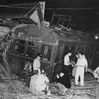 暴走した電車のわきで、検証作業をする人たち=東京都三鷹町(当時)で1949年7月