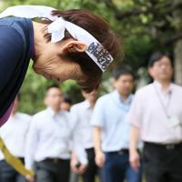 控訴断念を訴えて通行人に頭を下げる女性=東京都千代田区で2019年7月8日午後0時37分、吉田航太撮影