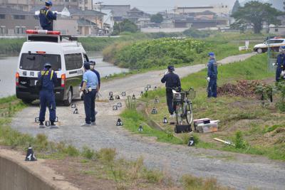 古賀容疑者が村尾さんの遺体を遺棄したとされる須恵川の現場付近を調べる捜査員ら。真ん中部分に写っているのは川から引き上げられた村尾さんの自転車=福岡県粕屋町で2019年7月8日、浅野孝仁撮影