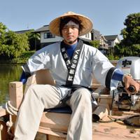 堀川遊覧船の史上最年少の船頭として、船を操りながら観光ガイドをする立石悠徒さん=松江市黒田町で、鈴木周撮影
