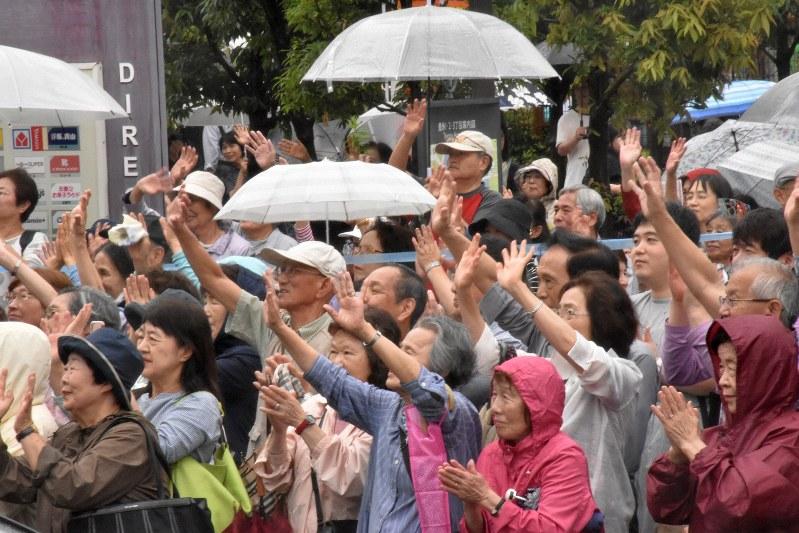候補の演説に手を振って応える人たち=東京都江東区で7月14日午後2時21分、須藤孝撮影