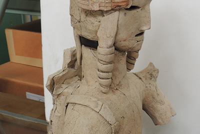 冠を着け、両耳の横に垂れる「みずら」と呼ばれる髪形をした「盛装した男子埴輪」。矢を入れる武具「靫」を背負うための帯が、右肩に巻き付ける形で表現されている=奈良県大和高田市で、大森顕浩撮影