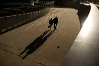 In this Sept. 27, 2018 file photo, an elderly couple walks past the Berlaymont building, the European Commission headquarters, in Brussels. (AP Photo/Francisco Seco)