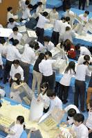 前回参院選で投票用紙を机に広げて開票作業にあたる自治体の職員ら=東京都中央区で2016年7月10日午後8時50分、北山夏帆撮影