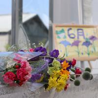 月命日に園入り口に設置される献花台には、事件から3年を前に色とりどりの花が手向けられていた。奥に見える建物は再生が進む津久井やまゆり園=相模原市緑区で6月26日、木下翔太郎撮影