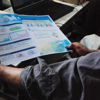 排出権取引のパンフレットを手に現金をだまし取られた悔しさをにじませる佐賀県の男性=同県みやき町で2019年7月11日、中里顕撮影