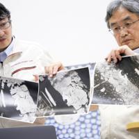 はやぶさ2が小惑星リュウグウに着陸したことを受けて行われた記者会見で公開された三枚の画像=相模原市中央区で2019年7月11日、吉田航太撮影