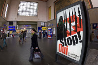 In this Nov. 4, 2009, file photo, people walk by a poster from the right-wing Swiss People's Party (SVP/UDC) depicting a woman wearing a burqa in front of a Swiss flag upon which are minarets which resemble missiles, at the central station in Geneva, Switzerland. Later in the month, a successful referendum banned the construction of new minarets in the country. (Salvatore Di Nolfi/Keystone via AP)