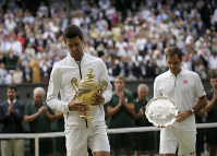 Serbia's Novak Djokovic and Switzerland's Roger Federer walk with the trophies after the men's singles final match of the Wimbledon Tennis Championships in London, on July 14, 2019. (AP Photo/Tim Ireland)