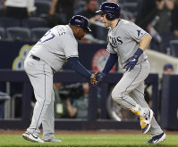 Tampa Bay Rays' third base coach Rodney Linares, left, congratulates Travis d'Arnaud after he hit a three-run home run off New York Yankees' closer Aroldis Chapma during the ninth inning of a baseball game on July 15, 2019, in New York. (AP Photo/Kathy Willens)