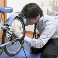 自転車に付着している物質を採取する雨宮正欣さん=埼玉県熊谷市で