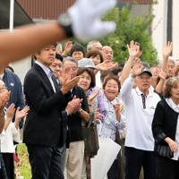 選挙カーから有権者に手を振る候補者や運動員=秋田市で、和田大典撮影