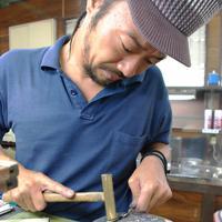 鉛の台の上にハサミを置き、真ちゅうのハンマーで刃をたたきながら微調整を繰り返す職人。「感覚」が全ての世界だ=兵庫県宝塚市で、川畑さおり撮影