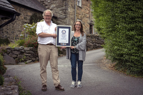 In this undated handout photo provided by Guinness World Records on July 16, 2019, Gwyn Headley and Sarah Badhan, stand on Ffordd Pen Llech with a certificate from Guinness World Records, confirming that the road is the steepest street in the world, in the seaside town of Harlech, North Wales. (Andrew Davies/Guinness World Records via AP)